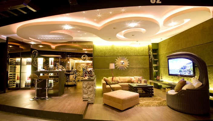 Large living room design for homes demanding better light with the use of false ceiling with use of wooden floors and special texture walls.